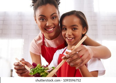 African American mother and daughter mix salad in kitchen. Healthy nutrition concept.