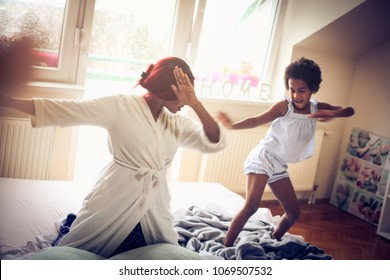 African American mother and daughter playing on bed. Space for copy.