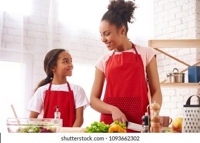 African American mother and daughter preparing salad in kitchen. Healthy lifestyle concept.