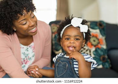 African American mother and daughter smiling at home.