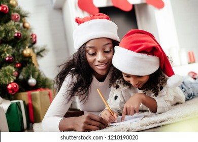 african american mother helping daughter to write letter for santa at home