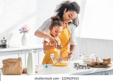 african american mother helping daughter whisking eggs for dough in kitchen