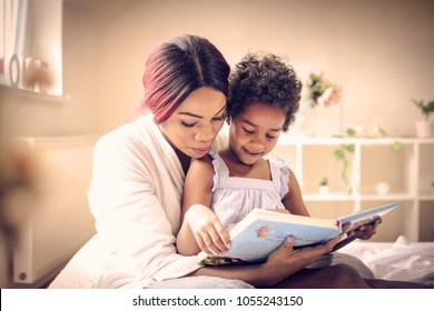 African American mother with her daughter in bed reading book together. Space for copy.