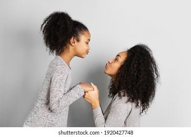 Afroamerikanische Mutter mit ihrer Tochter, die sich einzeln auf neutralem grauem Hintergrund anschaut.