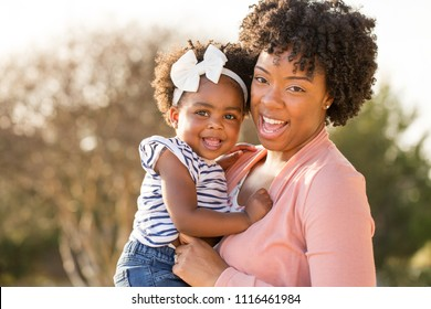 African American mother holding her daughter smiling.