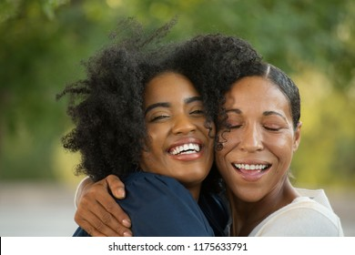 African American mother hugging her daughter at her graduation.