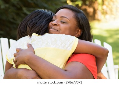 African American mother hugging her daughter.