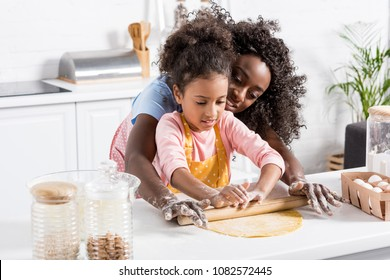 african american mother and kid rolling dough with rolling pin together on kitchen