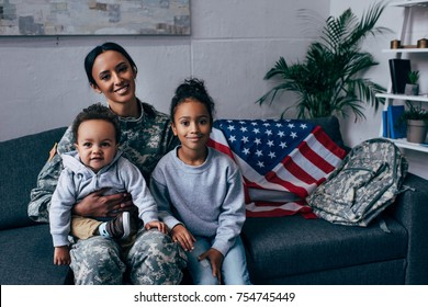 african american mother in military uniform sitting with her kids, american flag on background