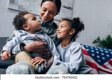 african american mother in military uniform sitting with her children, american flag on background