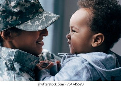 african american mother in military uniform with her little son at home
