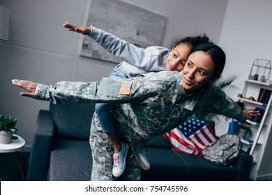 african american mother in military uniform piggybacking her daughter at home