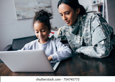 african american mother in military uniform and daughter using laptop at home