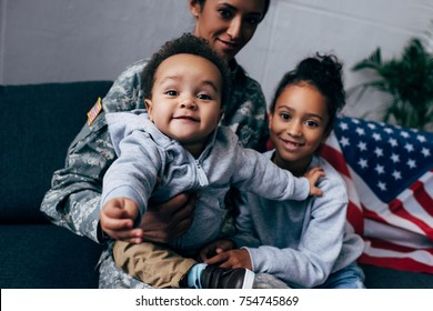 african american mother in military uniform sitting on sofa with her little son and daughter