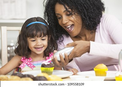 African American mother and mixed race daughter having fun frosting icing cup cakes