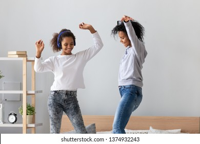 African American mother with phone in hand and teen daughter wearing headphones dancing to favorite music on bed together, having fun, mum and child jumping, enjoying funny activity at home