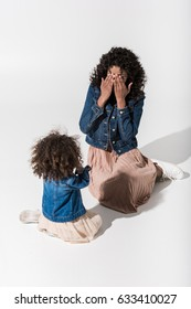 African american mother playing hide-and-seek with her baby girl daughter