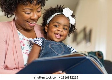 African American mother reading a book to her little girl.