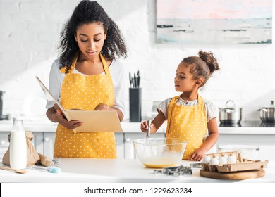 african american mother reading cookbook and daughter preparing dough in kitchen