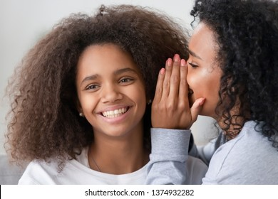 African American mother whispering to smiling teen daughter ear, enjoying free time, having fun at home, black mum or nanny gossiping with teenage girl, telling funny secret, rumor, close up