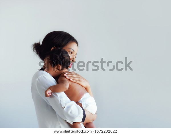 African American mum is comforting a baby on a white background.