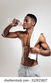 African american muscular man drinking water after sports training