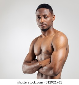 African american muscular man with hands crossed on grey background