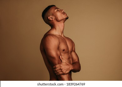African american muscular man standing on brown background. Fit man standing with eyes closed.