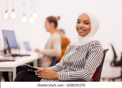 African american muslim girl with hijab working on a tablet in modern office. Caucasian girl and boy colleagues in the background