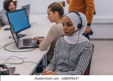 African american muslim girl with hijab and headset working  as customer support in a modern office.