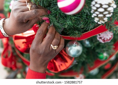 African American Nigerian Woman decorating her christmas tree for the yuletide fesive season