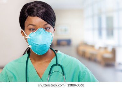 African American nurse at hospital with mask covering her mouth and stethoscope.