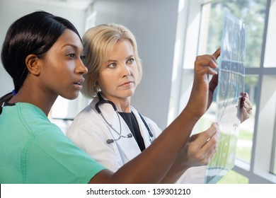 African American nurse in scrubs and Caucasian doctor in scrubs and white lab coat looking at an x-ray in brightly lit  hospital..
