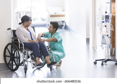 African American nurse in scrubs with patient in hospital wheelchair in corridor of specialist care clinic