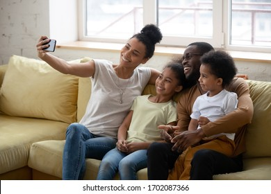 African American parent with two kids taking selfie, smiling woman holding phone, happy husband with son and daughter posing for photo with wife, family having fun together with gadget.