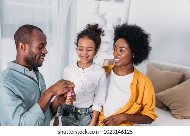 african american parents and daughter making soap bubbles at home