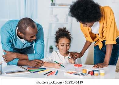 african american parents helping daughter drawing at home