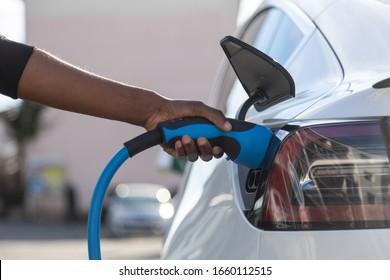 Afroamerikaner stecken ihr Elektroauto an der Ladestation an