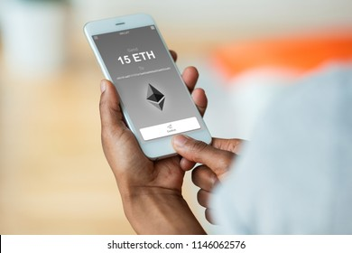 African american person sending a ethereum crypto transaction using  mobile phone wallet - Black people