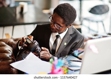 African american photographer paparazzi man wear on black suit and glasses sitting at office with camera and working behind laptop.