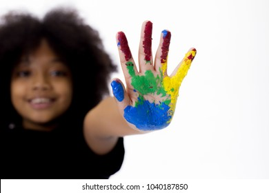 African American playful and creative kid getting hands dirty with many colors - in white isolated background