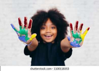 African American playful and creative kid getting hands dirty with many colors - in white brick background.
