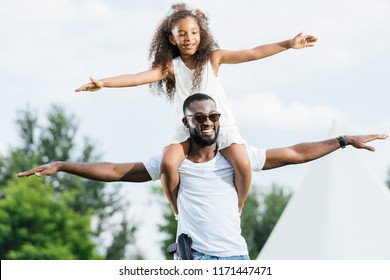 african american police officer with gun holding daughter on shoulders and they pretending flying in park