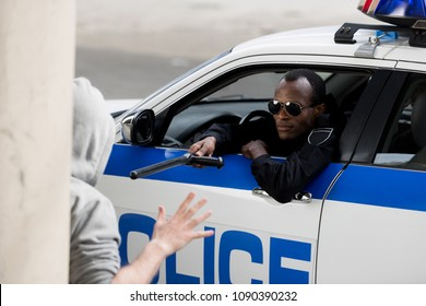 african american policeman stopping hooded man with police bat while looking out window