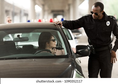 african american policeman talking to young woman sitting in car