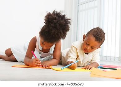 African american preschoolers drawing on the floor