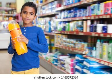 African American preteen boy standing with bottles of soda drinks in supermarket
