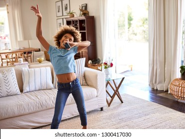 African American pre-teen girl dancing and singing along to music in the living room at home using her phone as a microphone, three quarter length