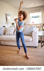 African American pre-teen girl dancing and singing in the living room at home using her phone as a microphone, full length, vertical
