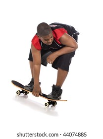 An African American preteen riding his skateboard while holding with one hand.  Isolated on white.